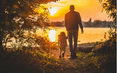a man walking towards a lake while holding the hand of sa small child